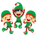Santa claus helpers dancing three little children dressed in costume happy on christmas eve time Royalty Free Stock Image