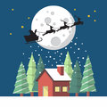 Santa Claus and his reindeer sleigh in silhouette against moon w Royalty Free Stock Photo