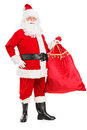 Santa Claus holding a bag full of gifts Stock Images