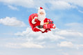 Santa claus holding a bag full of presents on clouds and sitting Stock Images