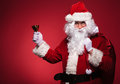 Santa claus holding bag on shoulder and a bell in his right hand red studio background Royalty Free Stock Photography