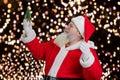Santa Claus holding decorative Christmas tree. Royalty Free Stock Photo