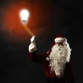 Santa claus holding a light bulb shining for thread Royalty Free Stock Photo
