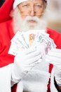 Santa claus holding money Arkivfoto