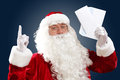 Santa claus holding and reading a letter to him Stock Photo