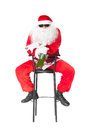 Santa claus holds a bottle of champagne sitting in chair wearing sunglasses and smoking cigar isolated on white background Royalty Free Stock Images