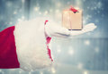 Santa claus holidng a small christmas present holding box in snowy night Stock Photos