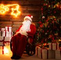 Santa claus in home interior sitting on rocking chair wooden with illuminated decoration on a wall Stock Photo
