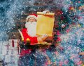 Santa claus in home interior wooden holding blank wish list scroll Stock Image