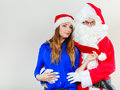 Santa Claus hugging woman with christmassy hat Royalty Free Stock Photo