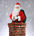 Santa claus inside chimney snowy background a brick with his bag of toys flung over his shoulder vertical format with a Stock Photos