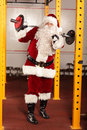 Santa claus lifting weights in gym physical condition training before christams time Stock Images