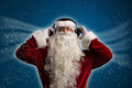 Santa claus is listening to music on headphones behind the abstract background Stock Photography