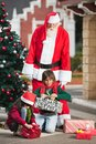 Santa claus looking at children opening christmas man dressed as presents in courtyard Royalty Free Stock Photo