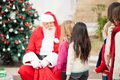 Santa claus looking at children standing in a queue outdoors Royalty Free Stock Photography