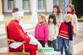 Santa claus looking at children standing in a side view of queue courtyard Royalty Free Stock Images