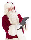 Santa claus looking at digital tablet while standing against white background Royalty Free Stock Photos
