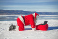 Santa Claus lying on the snow, looking at laptop news Royalty Free Stock Photo