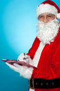 Santa Claus making notes in the wish list Royalty Free Stock Photos