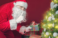 Santa claus mettant le boîte cadeau ou le présent sous l arbre de noël Image stock