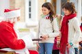 Santa claus offering biscuits and milk to children in courtyard Stock Photography
