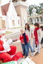 Santa claus offering biscuits to children in courtyard Royalty Free Stock Photo