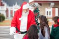 Santa claus offering cookies to children in courtyard Royalty Free Stock Image