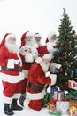 Santa claus outfits decorating christmas tree Lizenzfreie Stockbilder