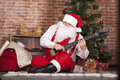 Santa claus plays the guitar on background of christmas tree and bag with gifts Royalty Free Stock Photos