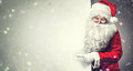 Santa Claus pointing on blank advertisement banner background with copy space Royalty Free Stock Photo