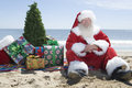 Santa claus with presents and tree que senta se na praia Fotografia de Stock Royalty Free