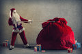 Santa claus pulls a huge bag of gifts lying around boxes with Royalty Free Stock Photos