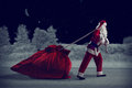 Santa claus pulls a huge bag of gifts in night winter forest pulling Royalty Free Stock Images