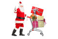Santa Claus pushing a shopping cart full of gifts Stock Photo