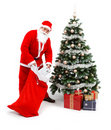 Santa Claus putting gifts under christmas tree Royalty Free Stock Image
