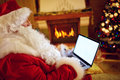 Santa Claus reading email on laptop with Christmas requesting Royalty Free Stock Photo