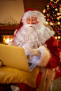 Santa Claus reading email on laptop requesting wish present list Royalty Free Stock Photo