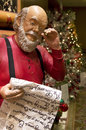 Santa claus reading the gift list and christmas tree background Stock Images