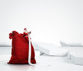 Santa claus reading long list sitting on a large sack and Stock Photo
