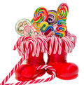 Santa Claus red boots, shoes with colored sweet lollipops, candys. Saint Nicholas boot with presents gifts. Royalty Free Stock Photo