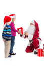 Santa claus in red costume giving present to beautiful girl little polite boy waiting on his turn standing together isolated over Royalty Free Stock Images