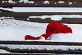 Santa claus red hat on bench with snow outdoors Royalty Free Stock Photo