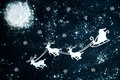 Santa Claus and reindeer flying through the night sky.