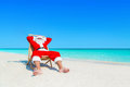 Santa Claus relax in sunlounger at sandy tropical sea beach Royalty Free Stock Photo