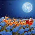 Santa Claus riding his reindeer sleigh flying in the sky Royalty Free Stock Photo