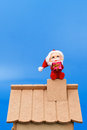 Santa Claus on roof holding a gift Royalty Free Stock Photography