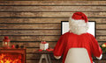 Santa Claus shopping online on computer from his warm room Royalty Free Stock Photo