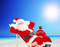 Santa claus sitting on a chair and relaxing on a beach sun Stock Photography