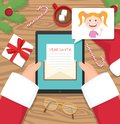 Santa claus is sitting at his workplace desk and receiving letter on his tablet from young girl