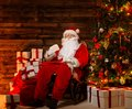Santa claus sitting on rocking chair in wooden home interior with letters in hands Royalty Free Stock Photos